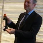 落札に成功したピーロート・ジャパンの代表取締役ローラン・フェーヴル氏。手にしているのはシャトー・ペトリュス!