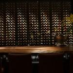「ドミニク・ルーム」のカウンター。こちらの壁はワインセラーで、色とりどりに見えるのはワインのボトルのキャップシール。